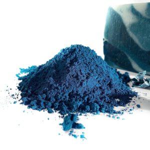 photo d'un tas de poudre de couleur bleu turquoise appelée Bleu Maya avec en arrière plant un savon de plusieurs nuances de bleu
