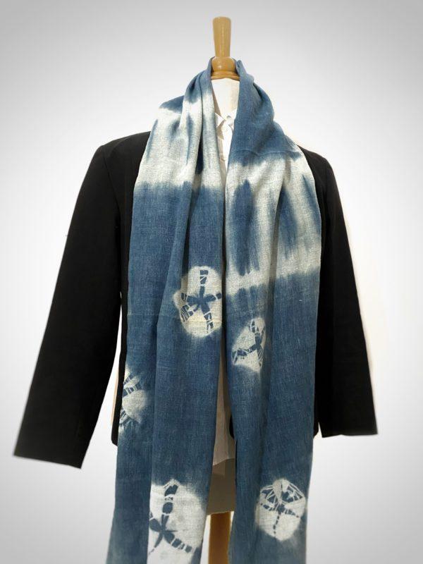 écharpe en soie sauvage fibre bio, teint artisanalement à l'indigo de Provence. Sur la photo l'écharpe est ouverte sur le mannequin et l'on peut voir cinq ronds blancs ainsi que deux bandes blanches sur fond bleu.