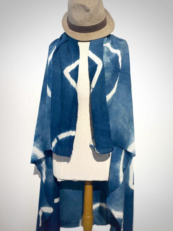 photo de paréo teint à la main avec de l'indigo le champ des couleurs , ouvert sur un buste de mannequin . Décoré d'un shibori , qui donne des motifs de losanges blancs