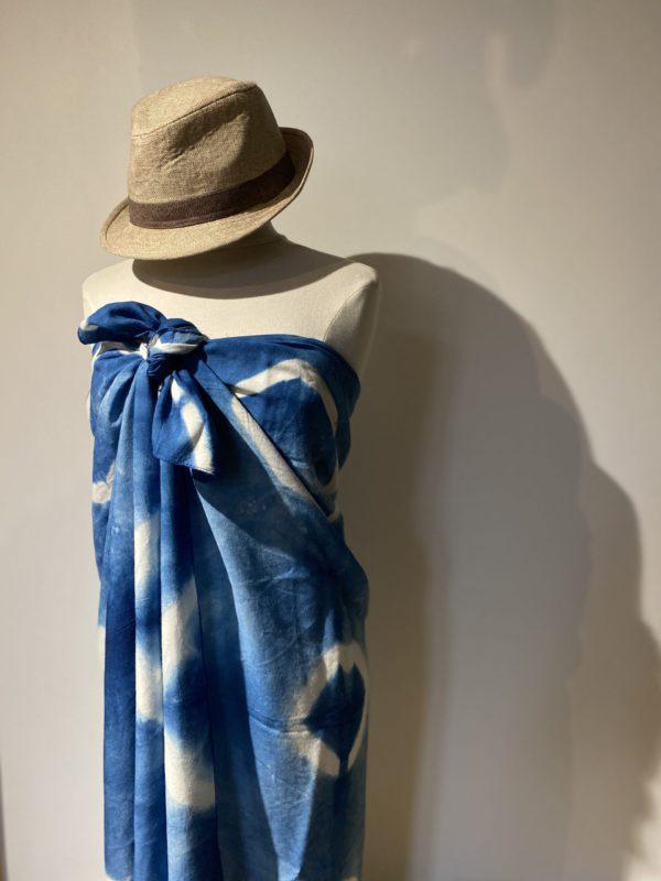 photo de paréo teint à la main avec de l'indigo le champ des couleurs , sur un buste de mannequin . Décoré d'un shibori , qui donne des motifs de losanges blancs