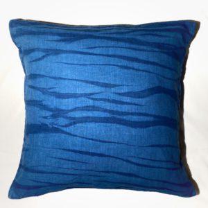photo de face d'une housse de coussin en lin fibre bio teint avec de l'indigo produit par le champ des couleurs. Les motifs sont zébrés bleu foncé sur un fond bleu plus clair