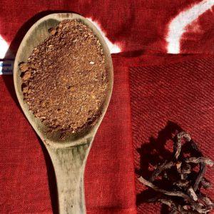 Photo d'une cuillère en bois contenant de la poudre rouge de garance des teinturiers, déposé sur plusieurs tissus de nuances de rouge différentes, ainsi qu'un petit tas de racines brutes