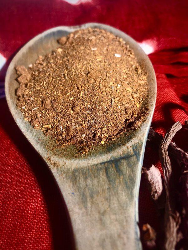 Zoom sur une cuillère de poudre de garance des teinturiers bio moulue, présenté sur un tissu rouge avec quelques racines entières.