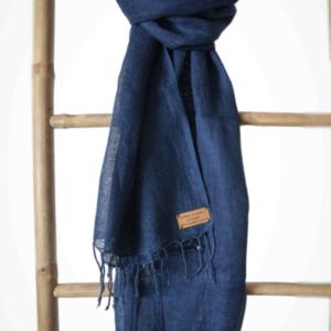 Photo d'une écharpe bleu foncé unie, en lin tissé à la main fibre bio, teint de manière artisanale à l'indigo bio et local, disposé sur une échelle.