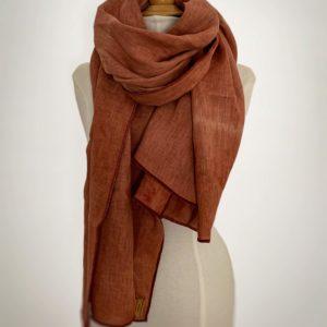 photo d'une écharpe en lin biologique , d'une couleur tomette de Provence réalisé avec de la garance et du cachou disposé autour du cou d'un mannequin